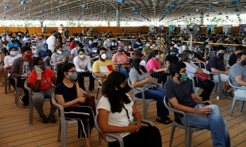 People wearing protective face masks wait to receive a dose of COVISHIELD, a vaccine manufactured by Serum Institute of India, at a vaccination centre in New Delhi on May 4.